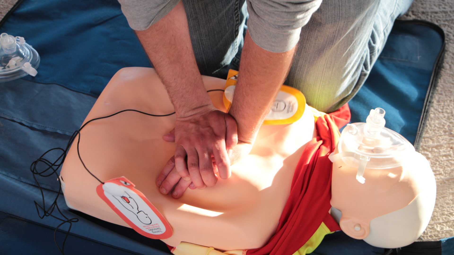 Person übt Herzmassage an Dummy aus