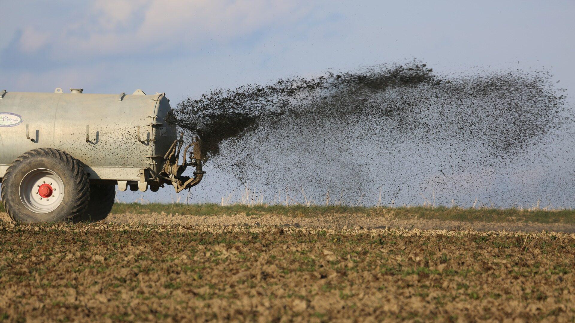 Traktor beim Ausbringen von Gülle