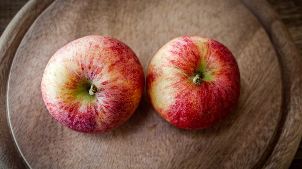 2 Gala-Äpfel auf Holzbrett