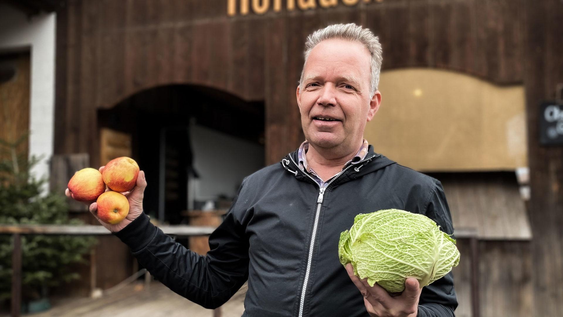Hofladenleiter mit Gemüse im Arm