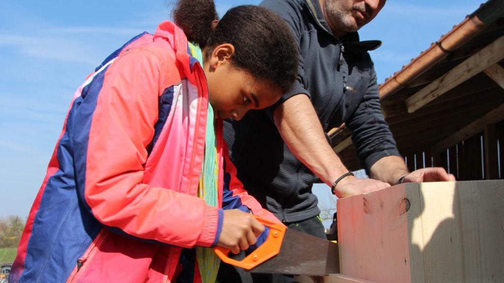 Mädchen sägt Holz