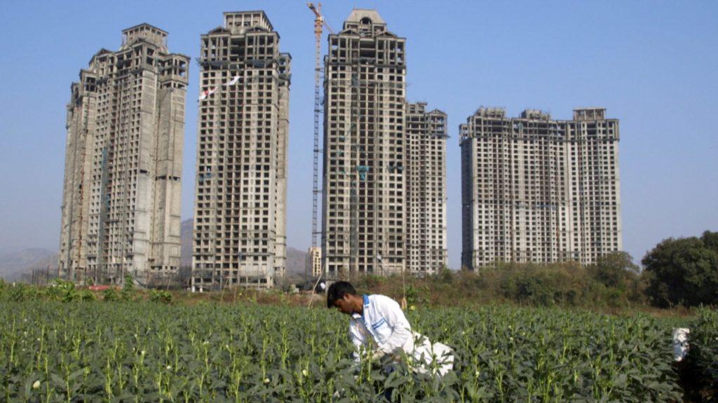 Mann auf Feld vor Hochhäusern